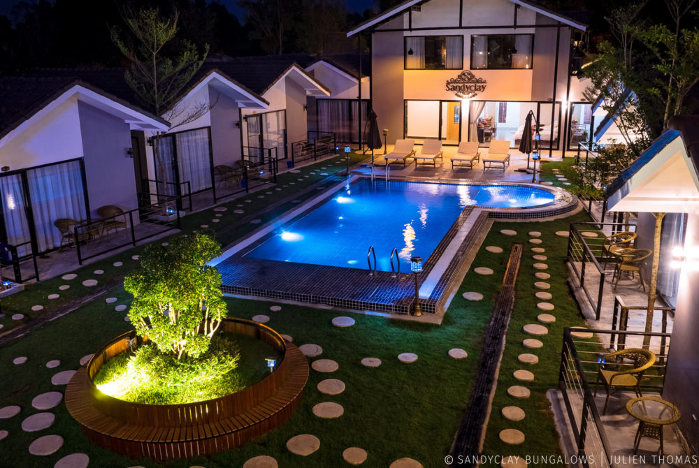 Central area designed with the bungalows and terasses for the guests, an illuminated swimming pool and a garden made with fresh grass in Sandyclay Bungalows.