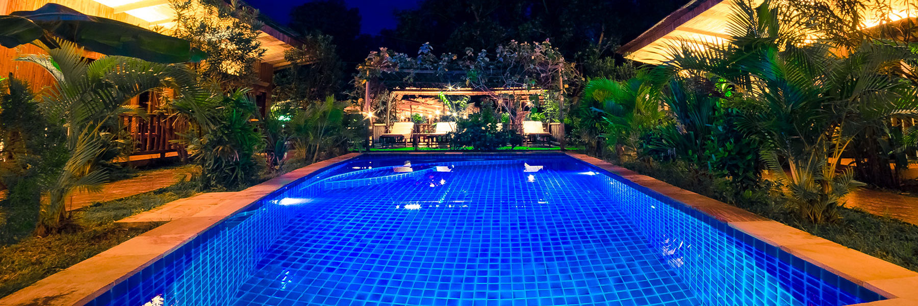 Central swimming pool with the tropical garden area at night and surrounded by the bungalows for the guests in Sok Sabay Resort, Otres Village - Cambodia.