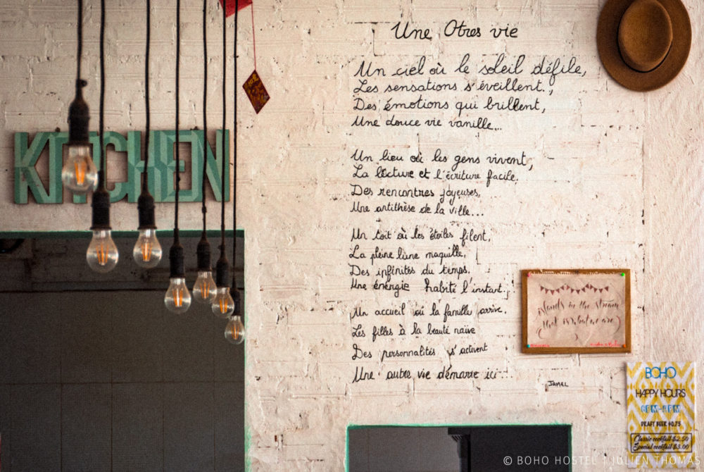 Stilly decoration with long lights from the ceiling and a French poem written on the kitchen's wall entrance in BOHO Hostel Kitchen and Bar, Otres Village.