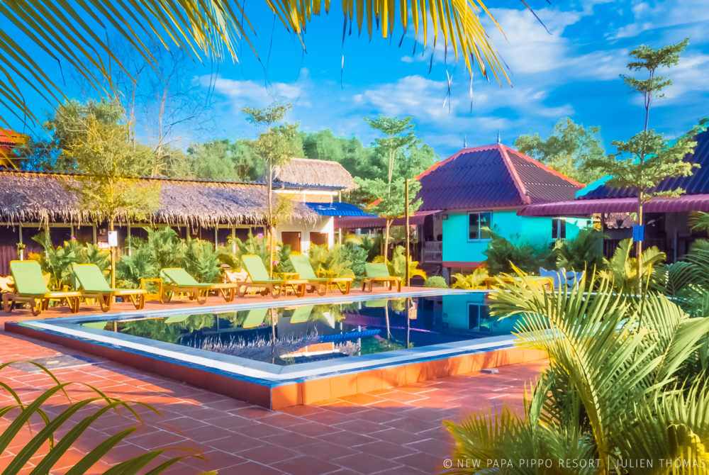 Central area designed with tropical vegetation and the bungalows for the guests witch are facing the swimming pool in New Papa Pippo Resort.