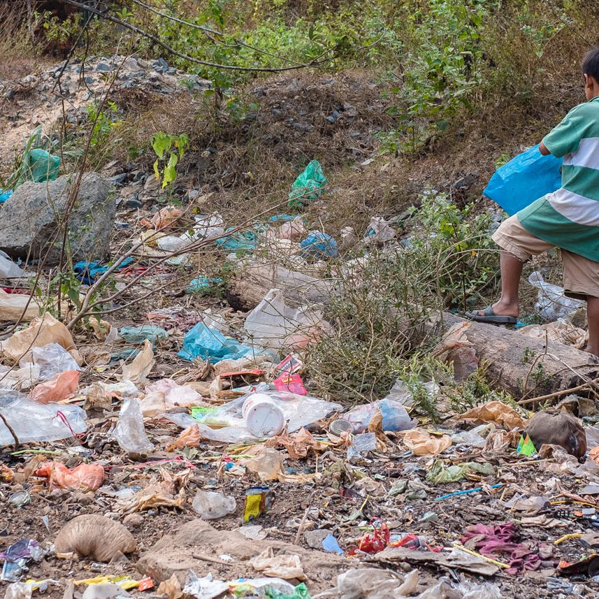 Underprivileged Cambodian kid is collecting discarded plastic waste in his living community during an ecological course - activity for children in Sihanoukville.
