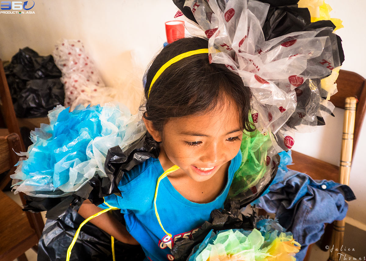 Young girl is playing and wearing large plastic waste flowers made from discarded waste during a craft course - fun filled ecological project in Happy Chandara.