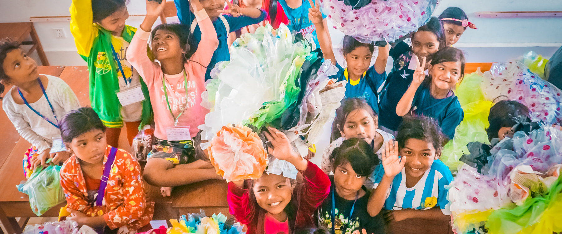 Cambodian participating children have finished to create giant plastic flowers from upcycled waste materials during a craft and recycle course in their school