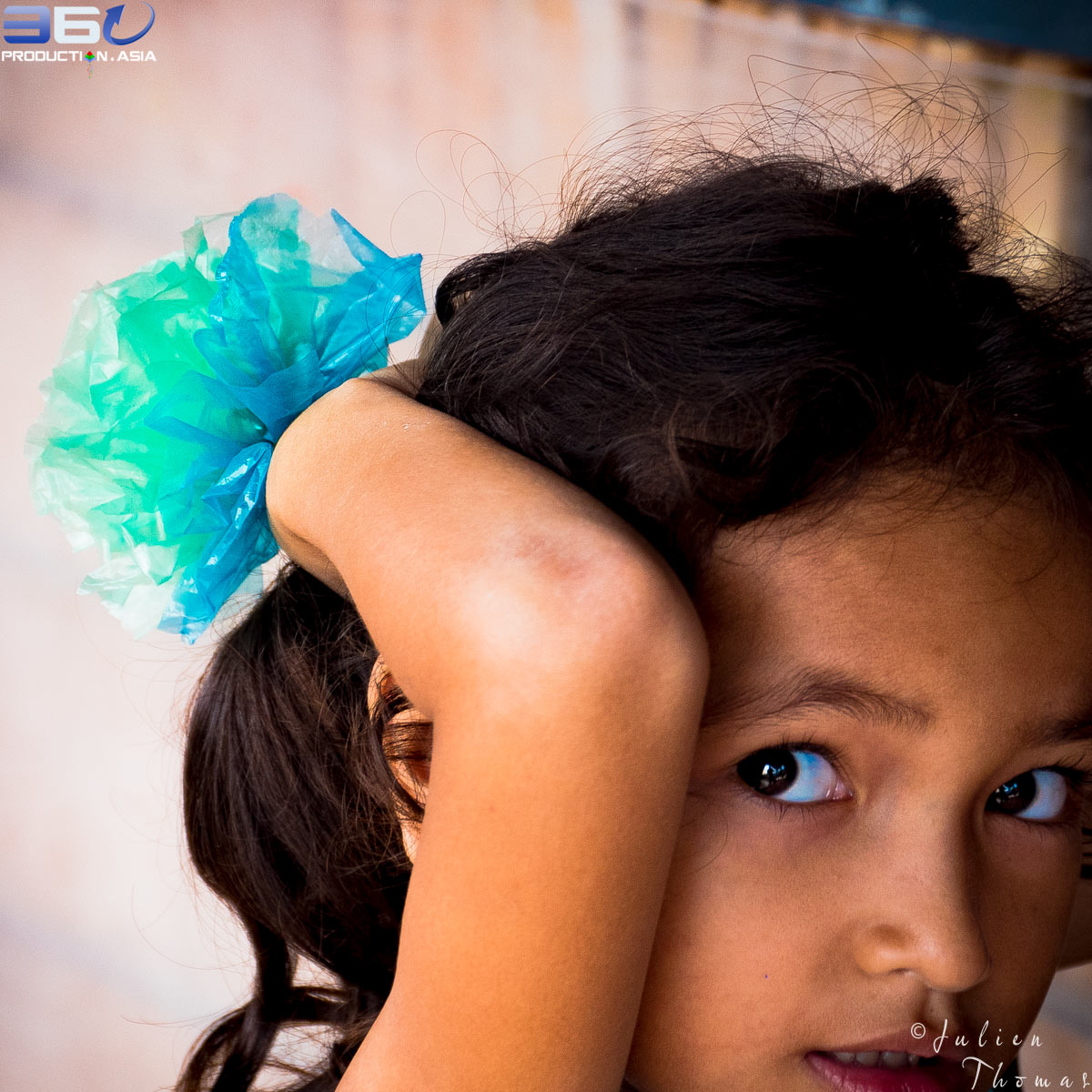 Young girl is tying a flower crafted from recycled plastic waste in her hair during a creative and upcycled course in GoodWill Center - Sihanoukville, Cambodia