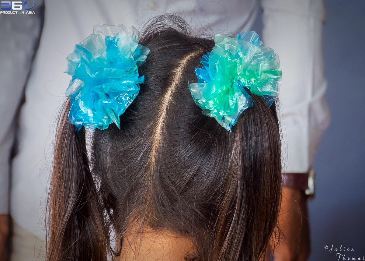 Cambodian child is wearing two hair bunches crafted with plastic waste - plastic bags during a creative and ecological children's course in Sihanoukville.