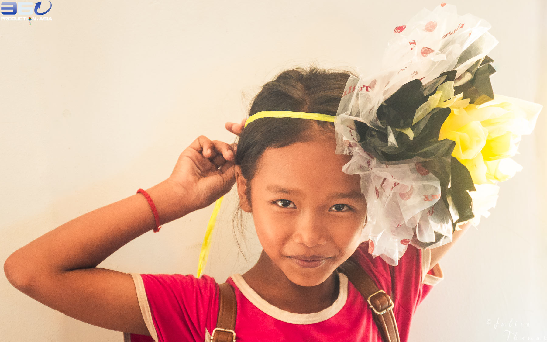 Happy kid is wearing a big flower made from plastic waste on her head and made during a craft course - fun filled ecological project in Phnom Penh, Cambodia.