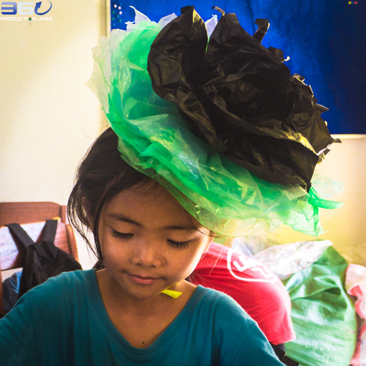 Young girl wearing a plastic flower as a hat made from plastic waste during a creative and ecological project by Julien Thomas