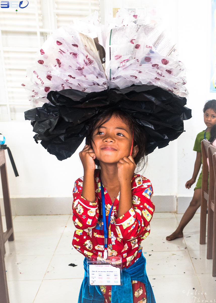Schoolgirl is wearing and playing with a giant flower made from upcycled waste material on her head during a creative and craft course in Happy Chandara School.