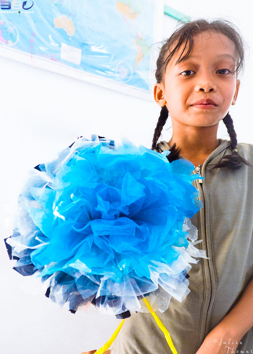 Khmer participating child is holding her large flower she crafted using recycled plastic bags - waste during a creative course for children in Phnom Penh, Cambodia.