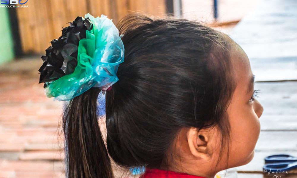 Cambodian girl is wearing a customized and homemade hair elastic crafted with recycled plastic bags, made up during a children's craft course in Sihanoukville