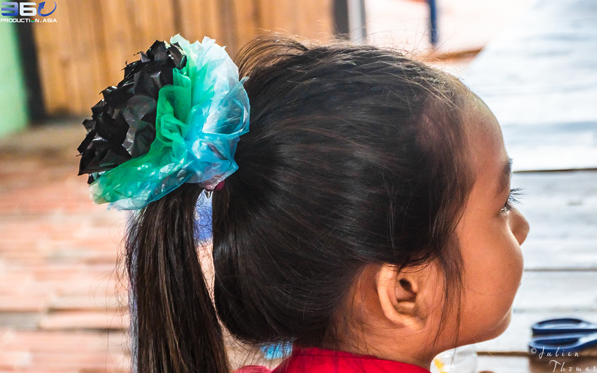 Cambodian girl is wearing a customized and homemade hair elastic crafted with recycled plastic bags, made up during a children's craft course in Sihanoukville.