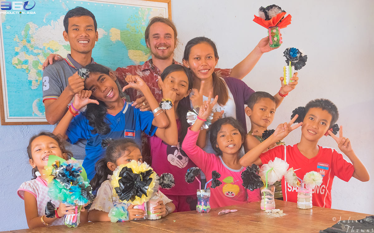 Participating children, teachers and Julien Thomas with the plastic flowers creations made from recycled bags in The GoodWill Center, Bomnong L'or Organization.