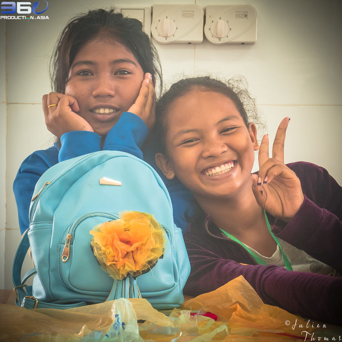 Khmer schoolgirls have hooked a crafted flower made from recycled plastic bags on a school bag during a ecological and creative children's course in Phnom Penh.
