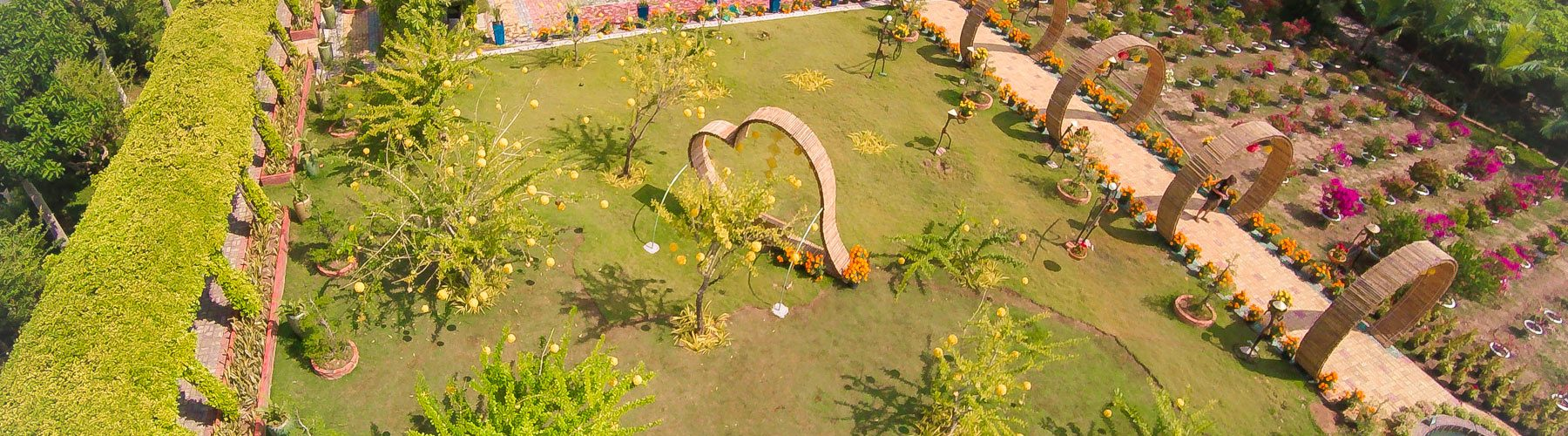Vietnamese garden resort with tropical trees, flower garden, a sculpted heart in the middle and a fountain, drone aerial photography by Julien Thomas