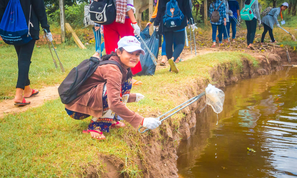 "Schoolgirl from NGO ""Toutes à L'école"" is picking up a discarded plastic bag in a river in Cambodia during a fun filled and ecological course by Julien Thomas."