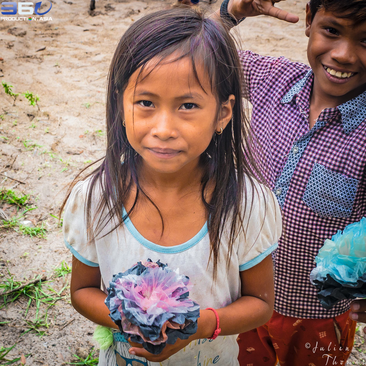 Schoolchildren holding their plastic flowers they have created from plastic waste during a filled ecological and crafty plastic waste project by Julien Thomas