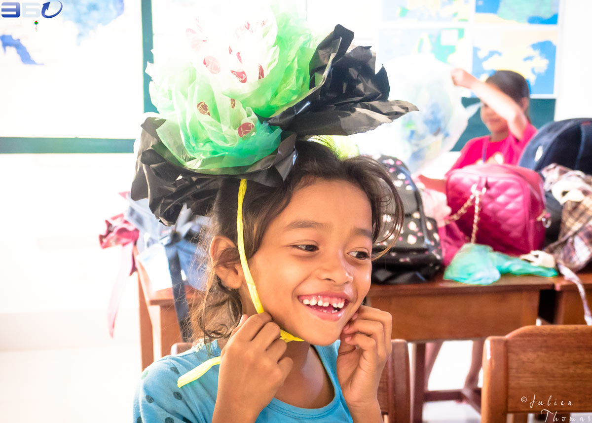 Cambodian schoolchild is playing - wearing on her head a large and crafted flower made from recycled plastic bags during a children's creative course at school