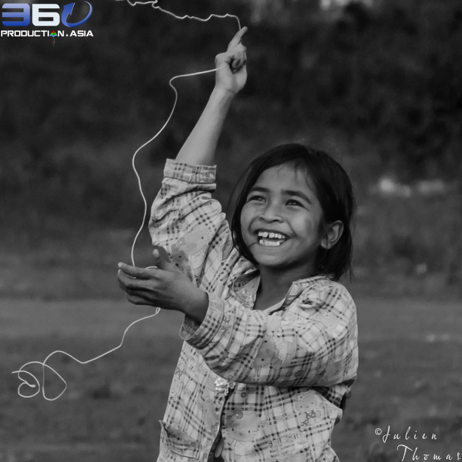 Happy orphan girl with a big smile play with a kite made during fun filled ecological project in Sen Monorom by Julien Thomas