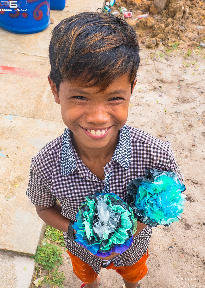Very happy underprivileged khmer schoolboy is holding crafted flowers he did made from recycled plastic bags - waste in Otres Village, Sihanoukville Province.