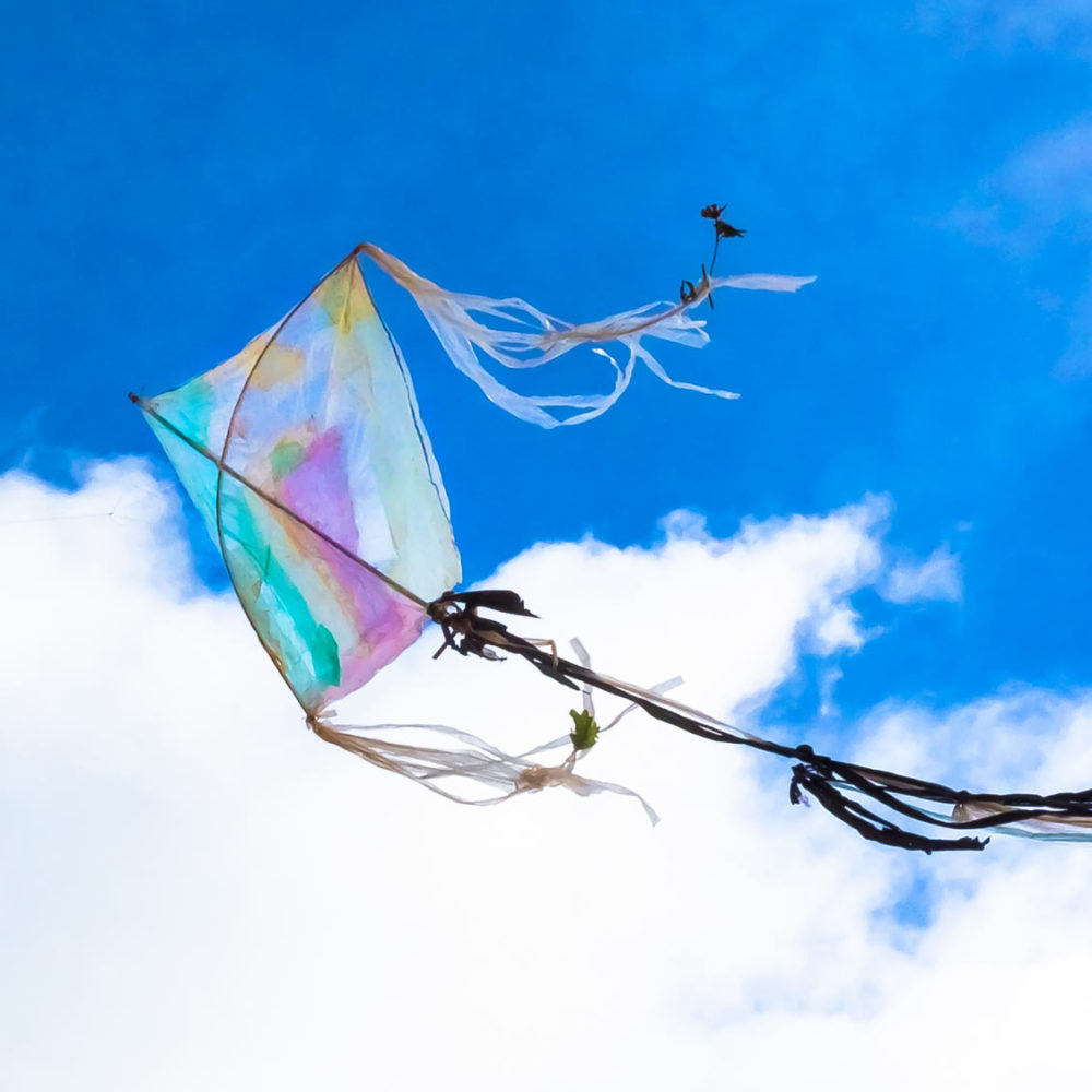 Square and large traditional Khmer kite designed, created, made with plastic waste is flying during an ecological and craft course for children in Cambodia.