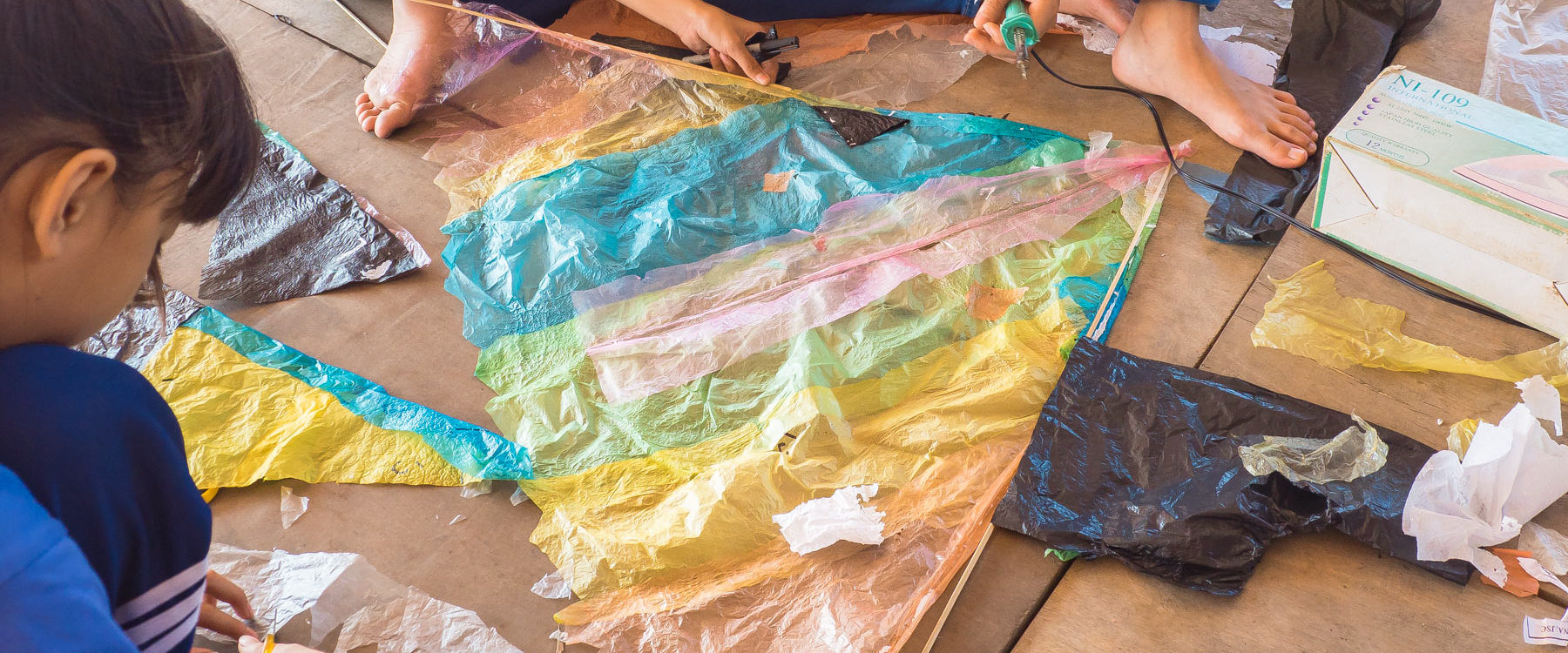Kite making with the participating schoolchildren, the multicolor cleaned plastic waste and bamboo sticks. It is easy to upcycle plastic into children's crafts.