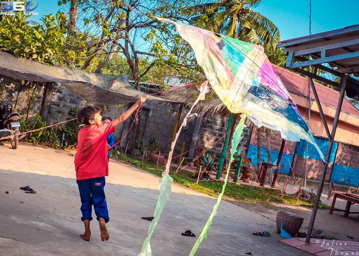 Cambodian kid playing in the schoolyard with a large and multicolor kite he made - created with plastic waste during a recycle project, course in Sihanoukville.
