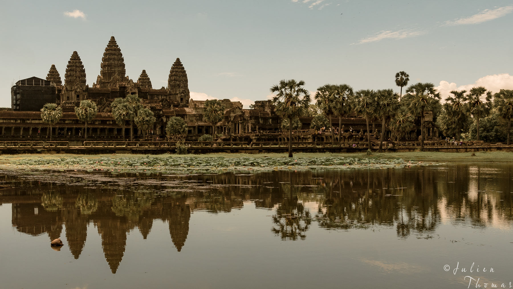 Overview of Angkor Wat entrance at the end of the day from across the lac with the ramparts. Photography Julien Thomas.
