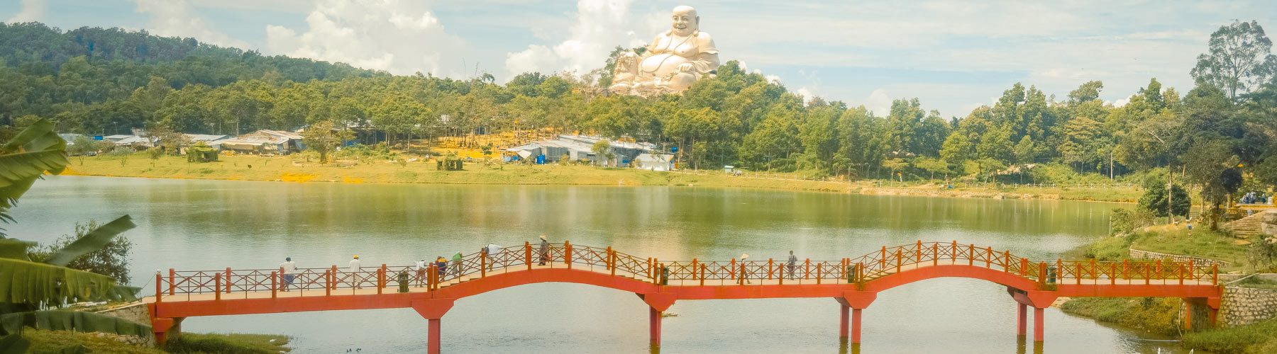 Top of Nui Cam mountain with a small red bridge and a lac facing a large sculpture of Budai, fat smiley Buddha in Vietnam. Photography by Julien Thomas.