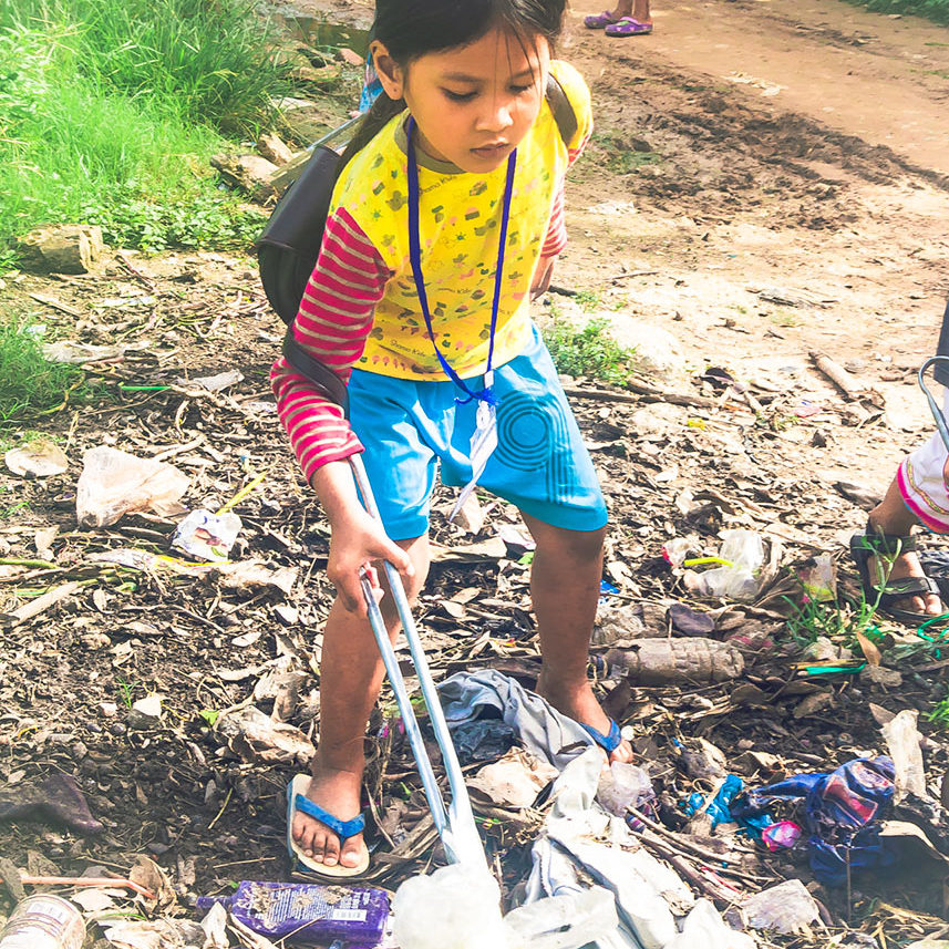 Cambodian schoolgirl is collecting discarded plastic waste on the ground for a fun filled ecological children's course at her school in Phnom Phen.