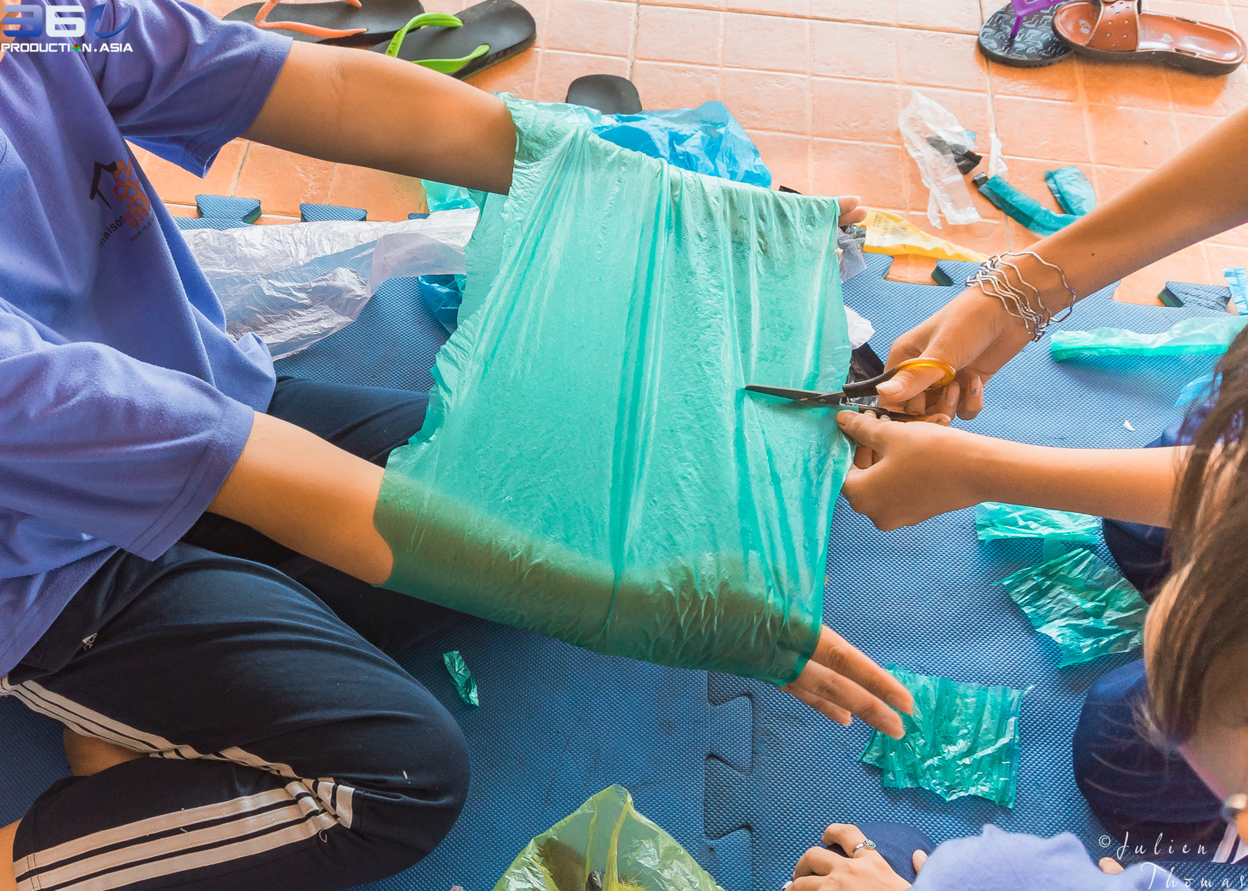 Students helping each others to work and cut the cleaned plastic waste to create children's crafts during a creative and ecological course in NGO Maison Chance.