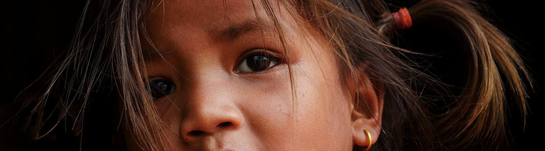 Young and pretty child from the Cambodian countryside with black eyes and earring in Kratie Province. Photography by Julien Thomas.