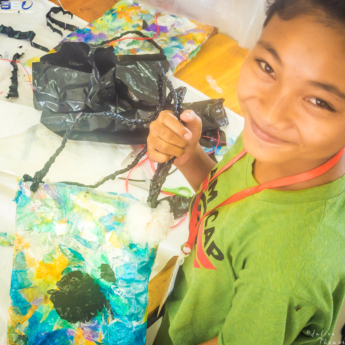 Schoolgirl with her children's purse crafted with plastic waste at school during a creative and ecological activity - course and project for children in Cambodia.