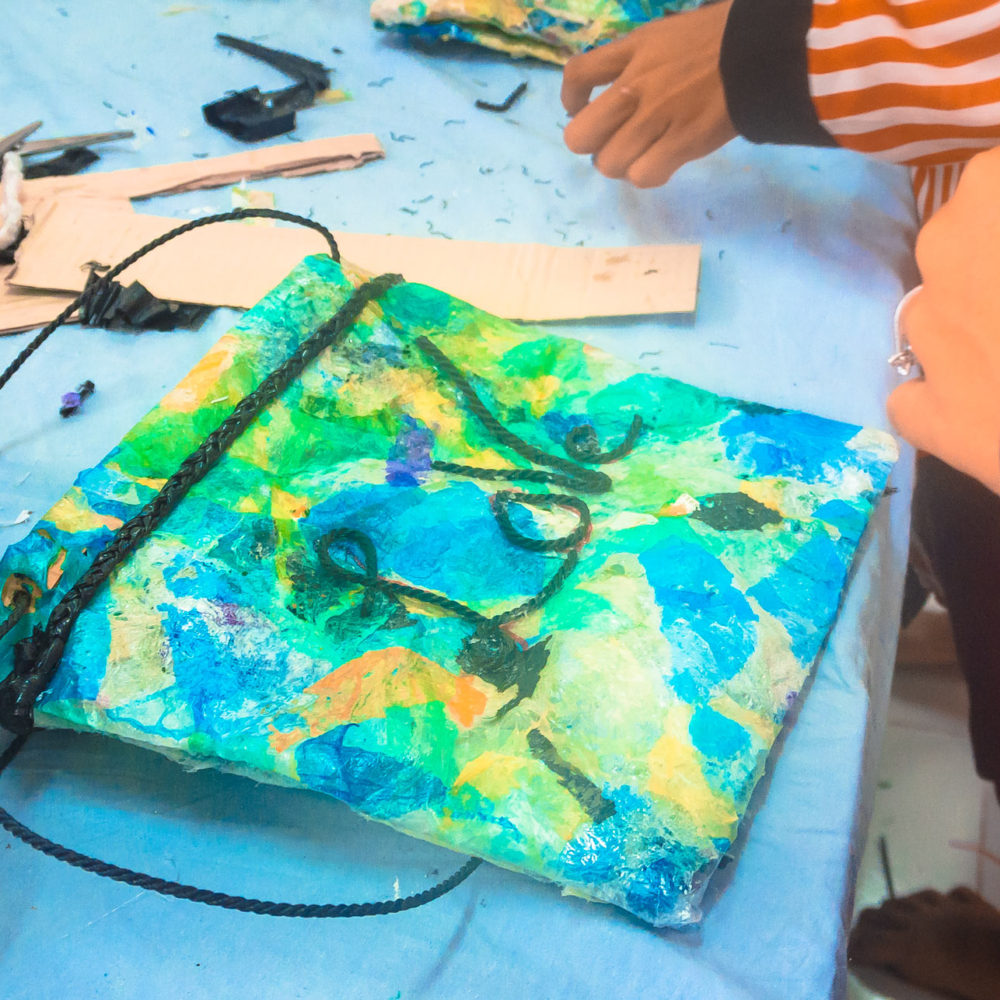 Finished and homemade children's purse from upcycled plastic waste material during a craft, creative and ecological course and activity for schoolchildren.