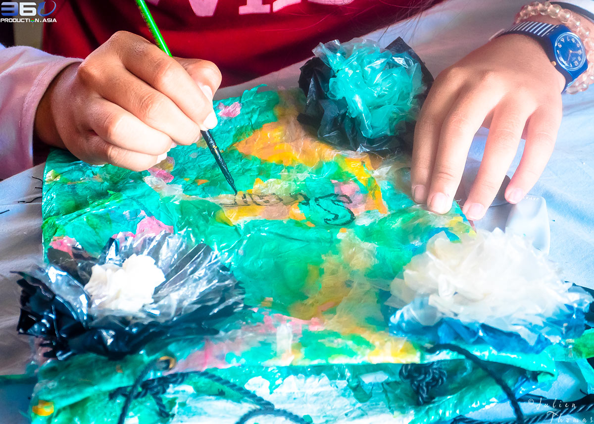 Child is painting and decorating her purse craft made recycled - upcycled plastic waste during a ecological and creative course - project for Cambodian children.
