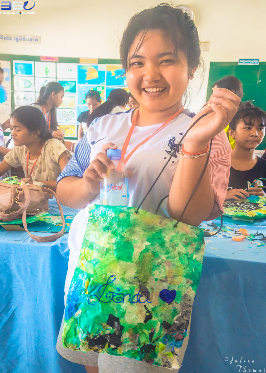 Schoolgirl with her homemade and customized children's purse from recycled plastic waste material made during a fun filled ecological and craft course in Cambodia.