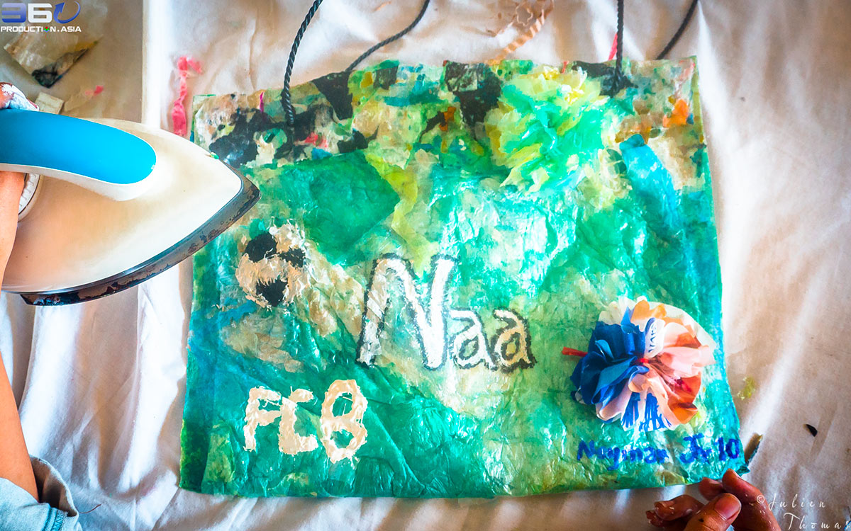Children's purse made from plastic waste with a plastic flower crafted during a creative and recycled project - course for schoolchildren in Cambodia.