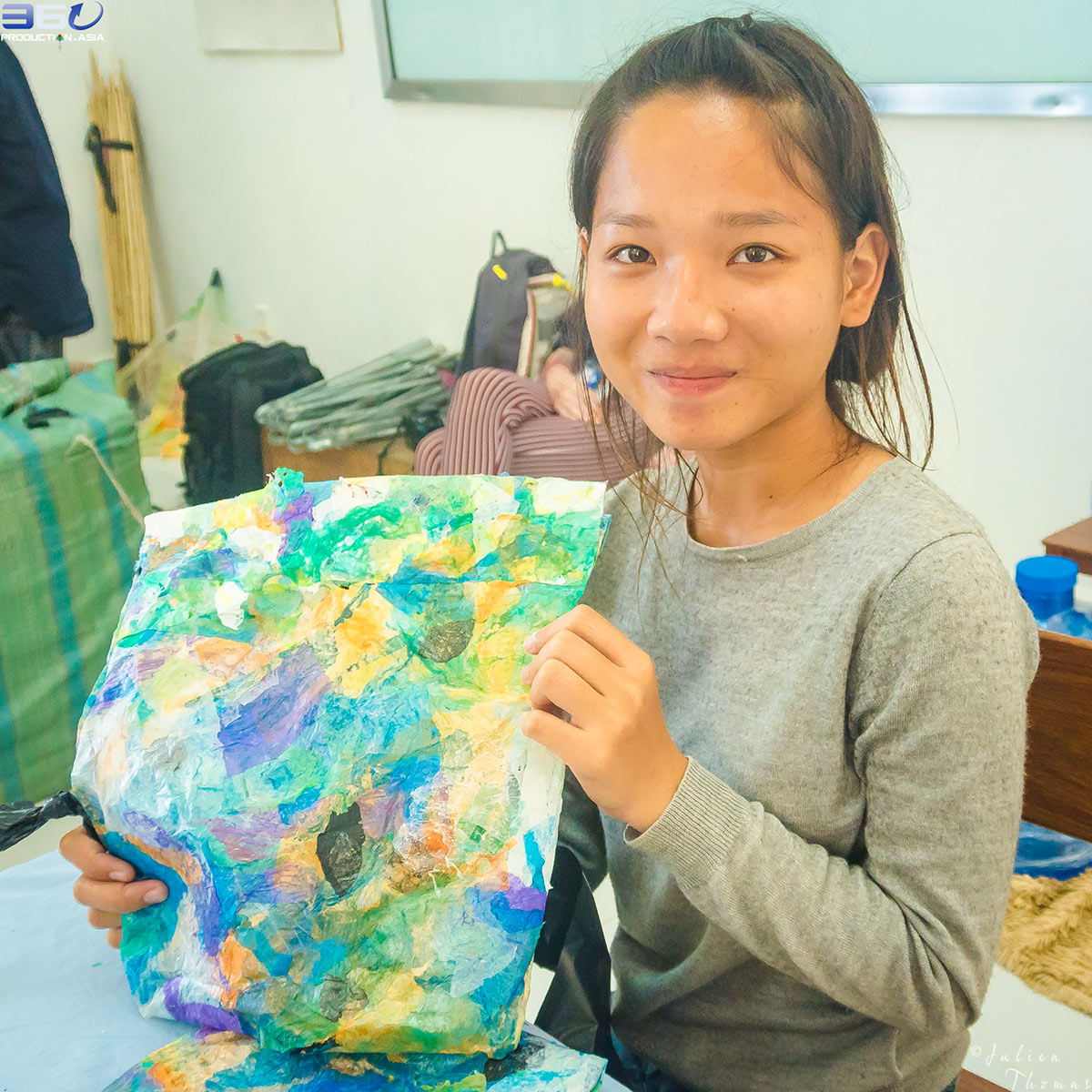 Cambodian girl is showing her homemade and multicolor purse crafted from recycled plastic waste material during a craft and ecological course in Phnom Penh.