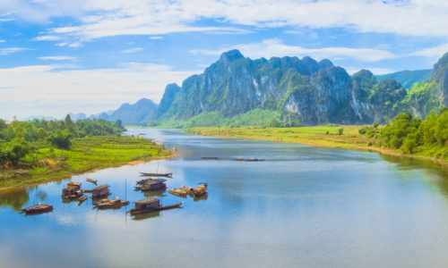 Vietnamese floating houses on large river with a green and hilly landscape in Vietnam. Photography by Julien Thomas.