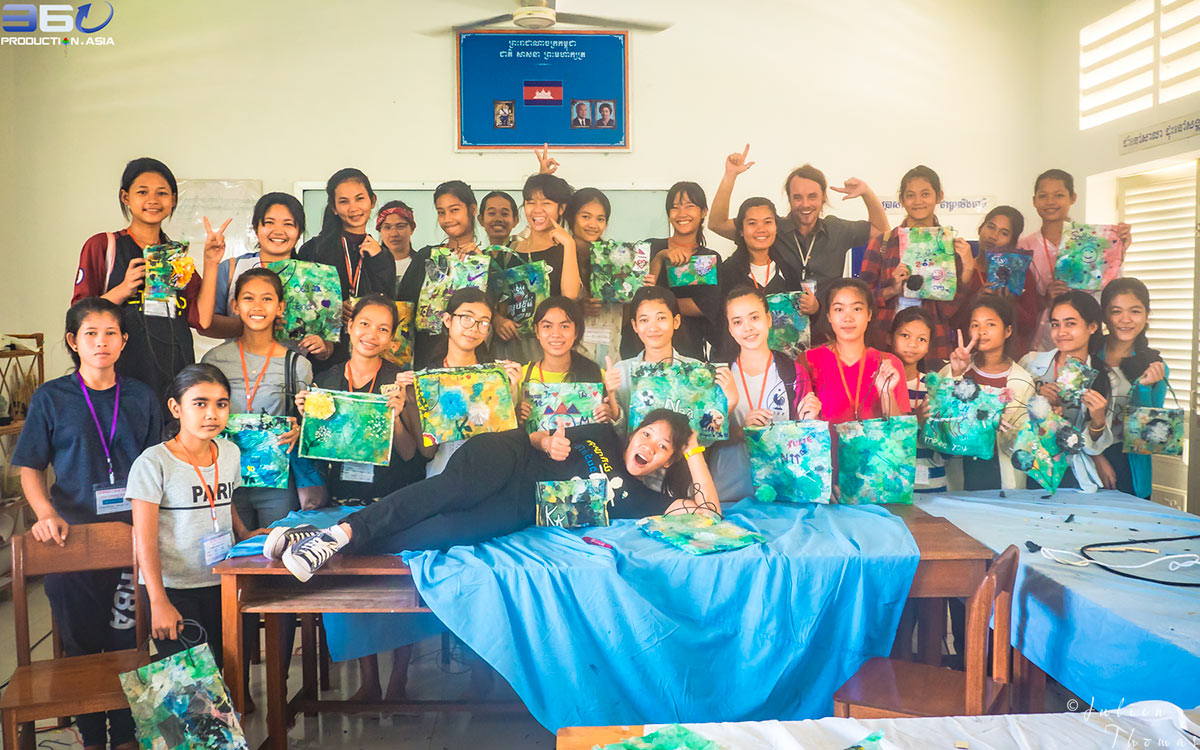 "Students from ""Happy Chandara"" school and Julien Thomas for a craft course focuses on creating children's purses from recycled plastic waste material in Phnom Penh."