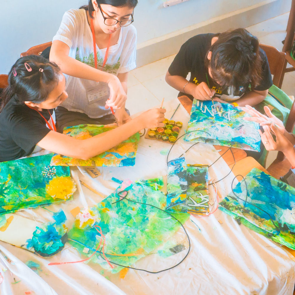 Kids are decorating and crafting their homemade purses from plastic waste - plastic bags during a creative and ecological course for schoolchildren in Phnom Penh.