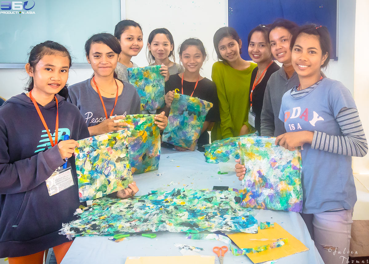 Group of participating students with their homemade purse crafted from plastic waste during a fun filled ecological course - project for children in Cambodia.