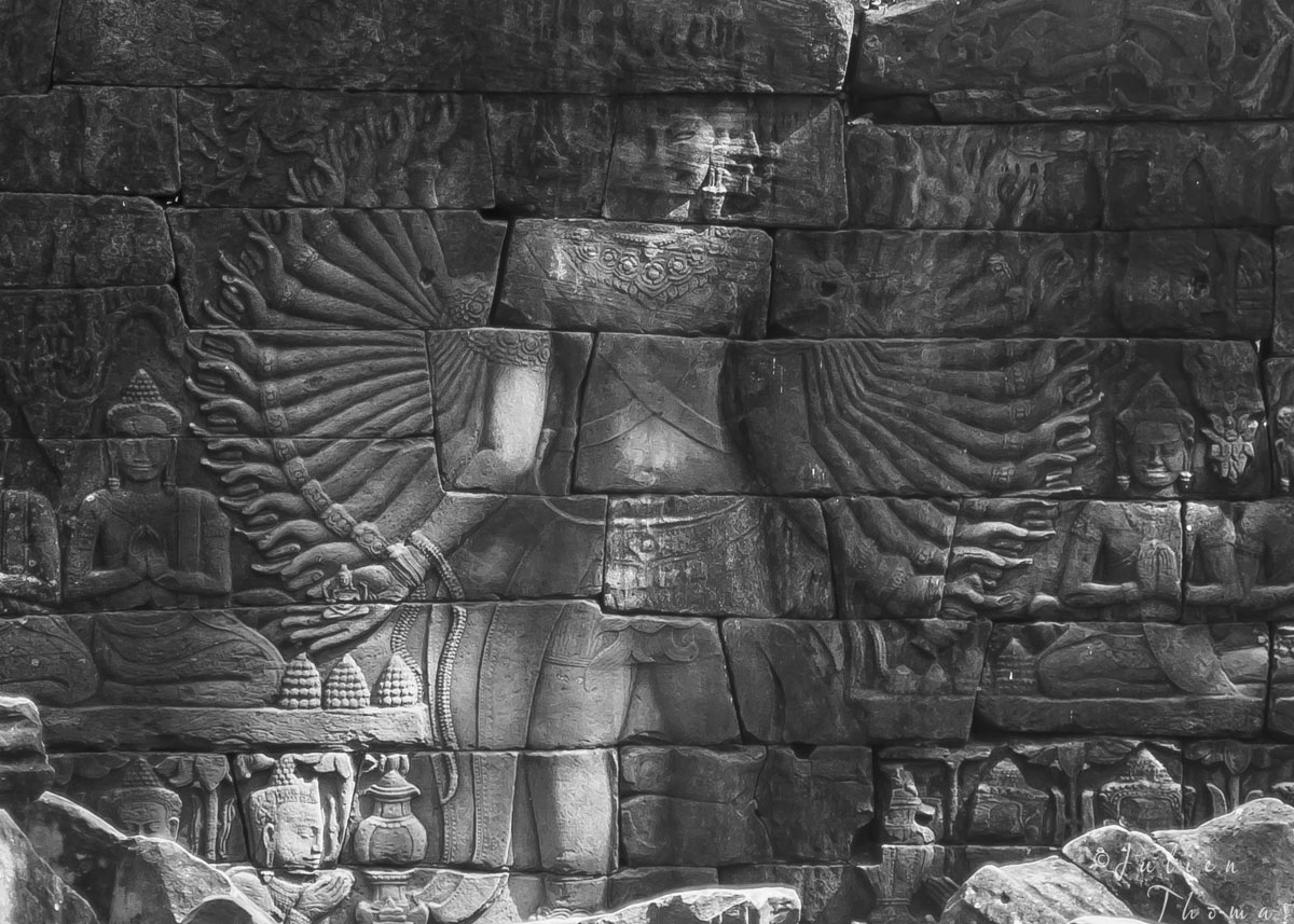 Goddess Avalokiteshvara 32 arms carving on stone wall in ruined temple in Banteay Chhmar archaeological site - Cambodia. Photography by Julien Thomas.