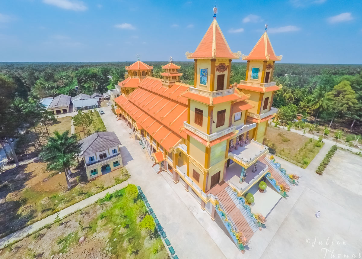 Brand new Cao Dai Temple in a countryside village surrounded by vegetation, only found in Vietnam. Drone - aerial photography by Julien Thomas.