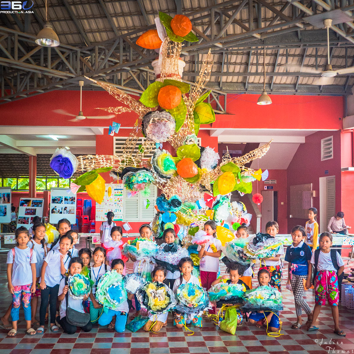 Participated schoolchildren whose have created large flowers from recycled plastic waste to hang on a crafted tree standing in Happy Chandara schoolyard.