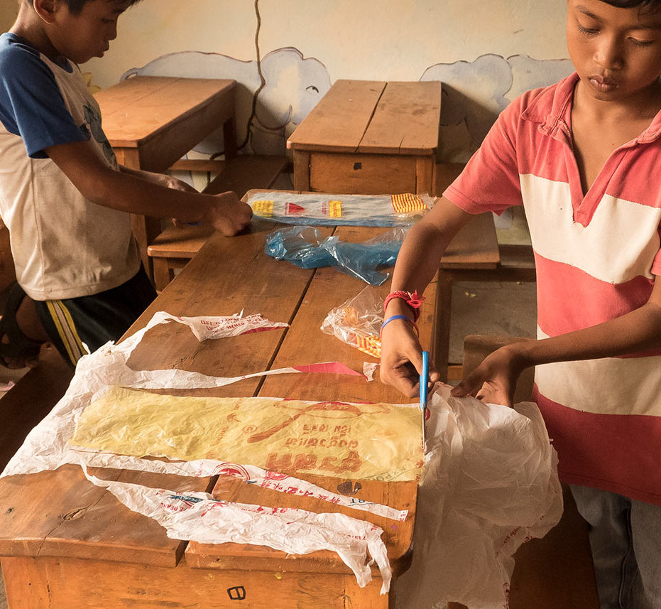 Underprivileged Cambodian schoolchildren are working with recycled plastic bags during a craft and creative course - project for children in Otres Village