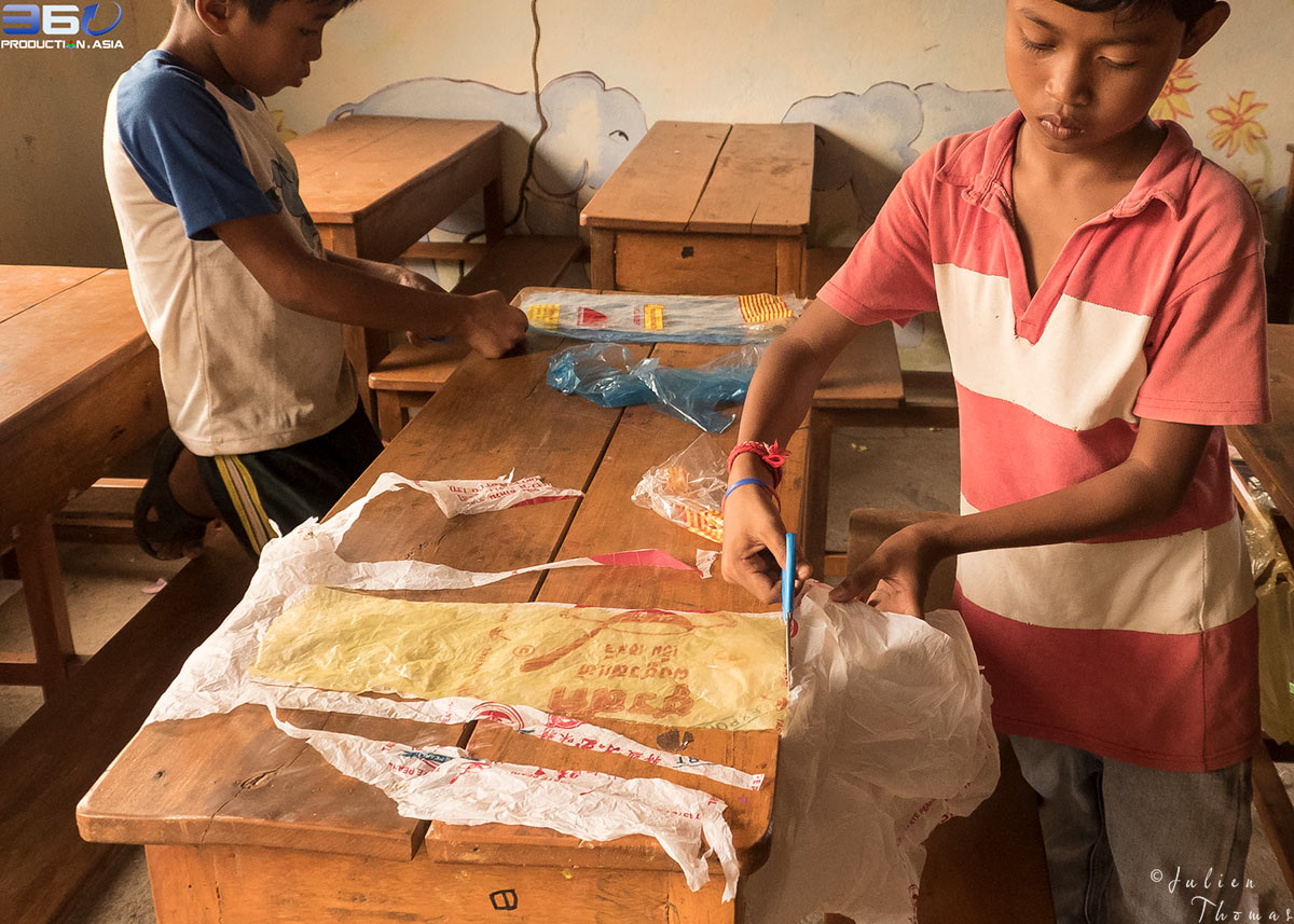 Underprivileged Cambodian schoolchildren are working with recycled plastic bags during a craft and creative course - project for children in Otres Village.