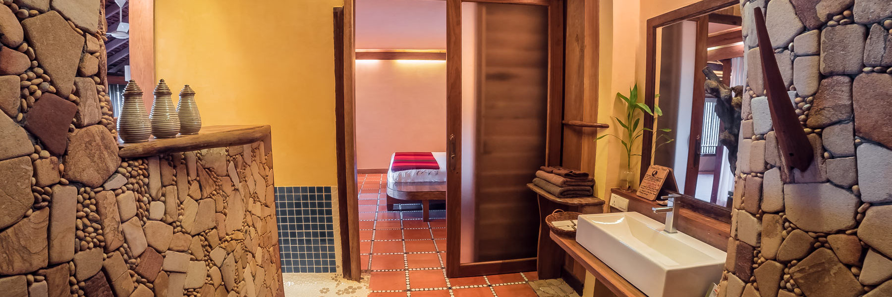 Residence Penthouse bathroom, designed with mineral stones and doors to the double bedroom and the private terrasse in Veranda Natural Resort, Kep - Cambodia.