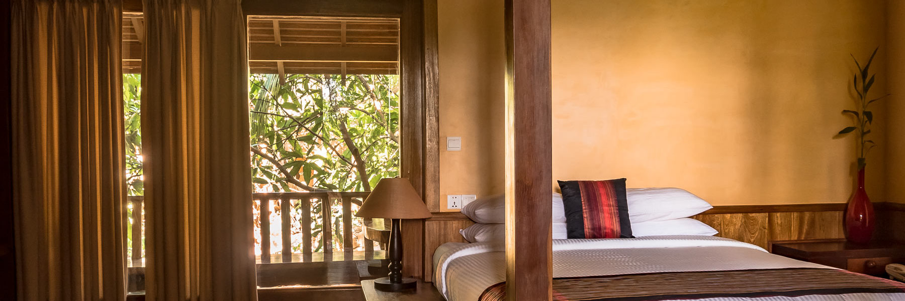 Pool Villa bedroom with a double bed, air conditioner and private terrasse to tropical vegetation view in Veranda Natural Resort, Kep - Cambodia.