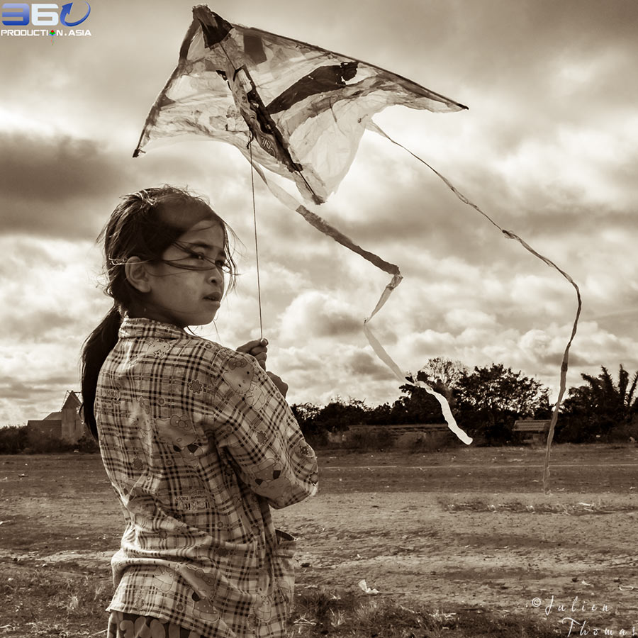 A Cambodian orphan is playing with her flying homemade kite created with recycled plastic waste during a fun filled ecological course in Sen Monorom