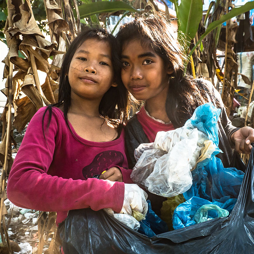 Schoolgirls are collecting discarded plastic bags in their school community during ecological course for children in The Goodwill Center, Sihanoukville.